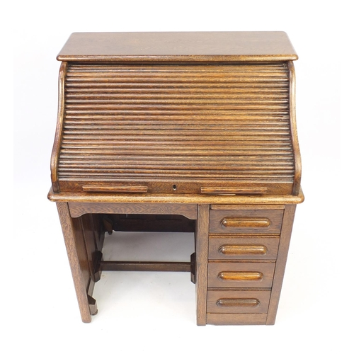 2033 - Oak tambour front roll top desk with four drawers to the base, 114cm H x 90cm W x 66cm D