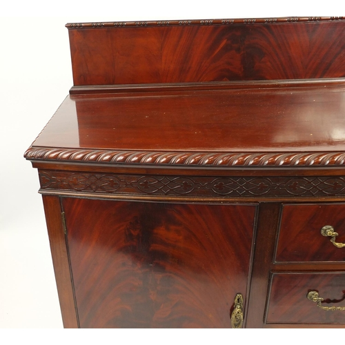 2021 - Chippendale style mahogany bow front sideboard fitted with two cupboard doors and three central draw...