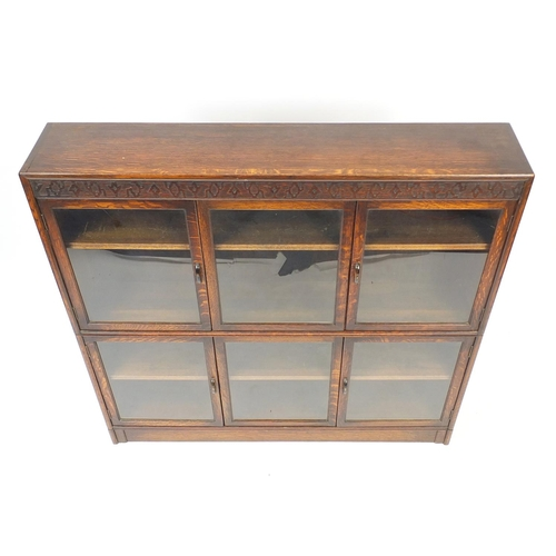 2037 - 1920's oak sectional bookcase by Gumm with four doors and two sliding panels, 125cm H x 128cm W x 25...
