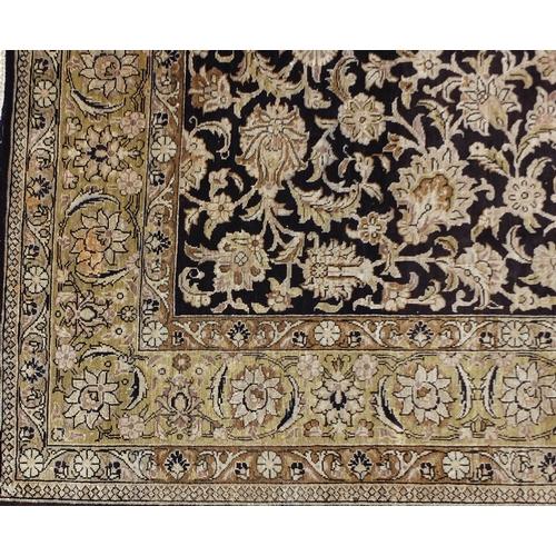 2026 - Rectangular Persian silk rug having an all over floral design onto a midnight blue ground, 160cm x 1...
