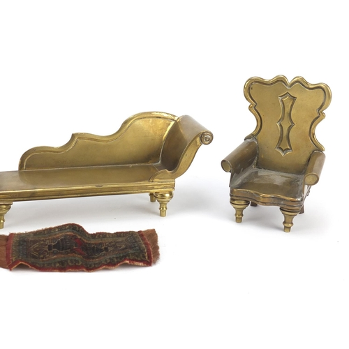 13 - Antique brass dolls house furniture and a rug comprising two chairs and a chaise lounge, the largest...