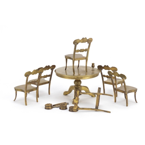 12 - Antique brass dolls house furniture comprising table and six chairs, the table 7.5cm high x 11cm in ...