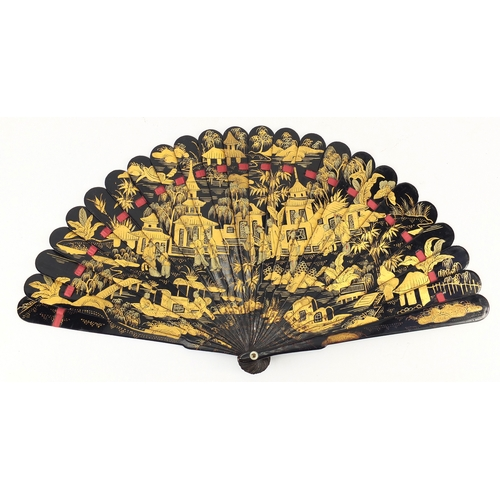 39 - Chinese black lacquer fan gilded with figures amongst pagodas and a river landscape, 20cm in length...