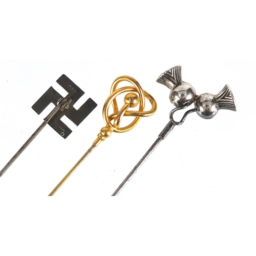 20 - Three hat pins including an unmarked gold and enamel swastika, the largest 25.7cm in length...