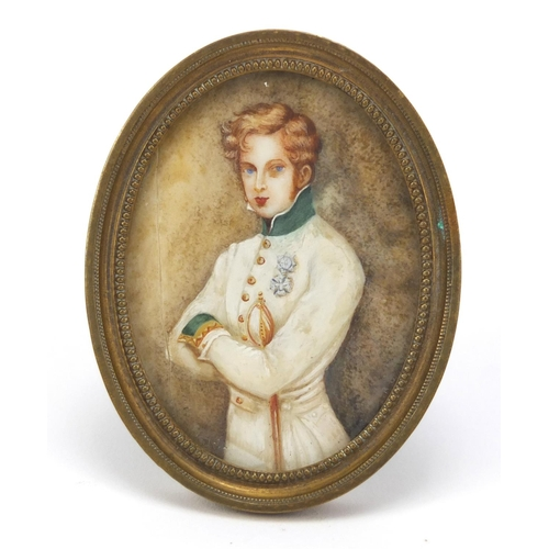 46 - Oval hand painted portrait miniature of a young gentleman in military dress, housed in a brass frame...