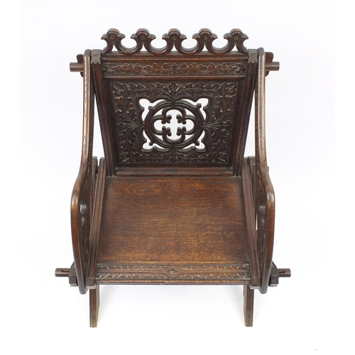 2033 - Gothic style oak hall chair with X-frame support carved with foliage, 88cm high