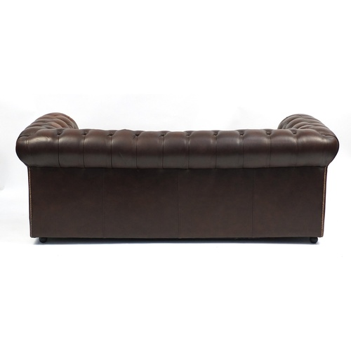 2011 - Brown leather three seater Chesterfield settee with buton back, 186cm wide...