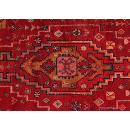 2055 - Rectangular Persian red ground rug having an all over geometric design, 210cm x 126cm