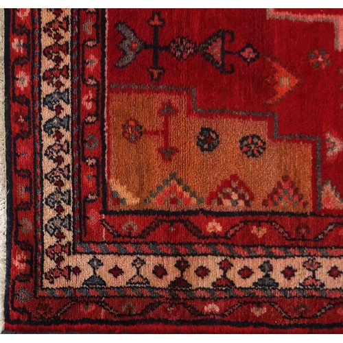2055 - Rectangular Persian red ground rug having an all over geometric design, 210cm x 126cm...