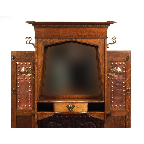 2005A - Arts & Crafts oak hall stand with bevelled mirror and copper inserts to each wing, remnants of the o...