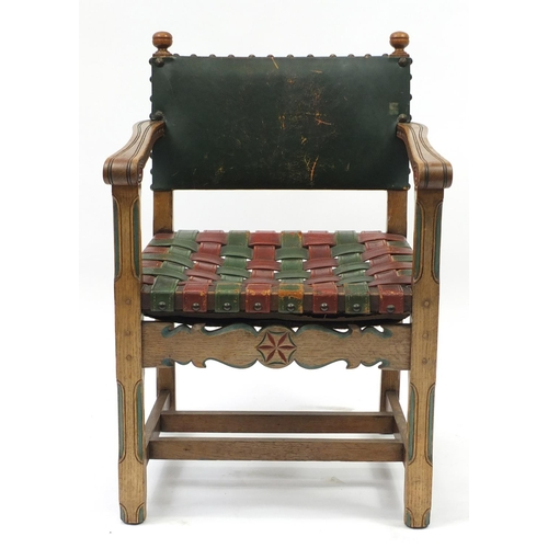 2046 - Carved oak open arm chair with red and green leather strap seat, 85cm high...