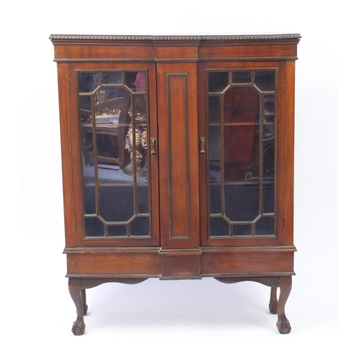 2004 - Mahogany breakfront bookcase fitted with a pair of glazed doors, raised on ball and claw feet, 133cm...