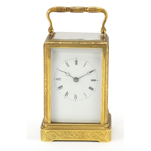 23 - 19th century brass cased carriage clock striking on a bell having an enamelled dial with Roman numer...