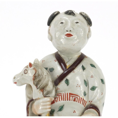32 - Chinese porcelain figure of a boy holding a toy horse hand painted with leaves, 20.5cm high...