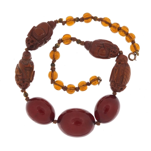 13 - Chinese cherry amber coloured bead and carved coquilla nut necklace, 40cm in length...