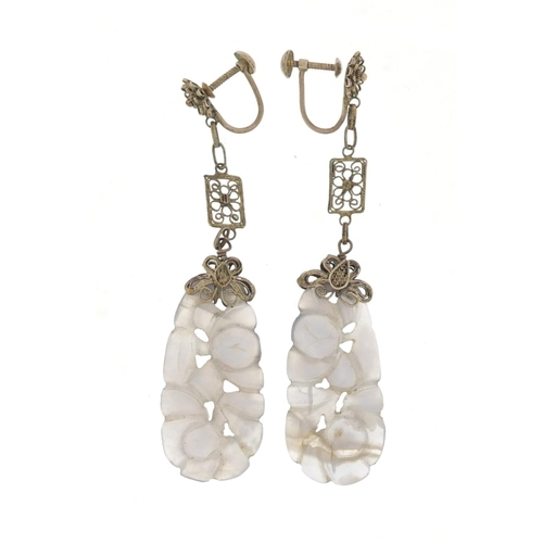 16 - Pair of Chinese white metal mounted agate earrings carved with flowers, 7.5cm in length, 9.8g...