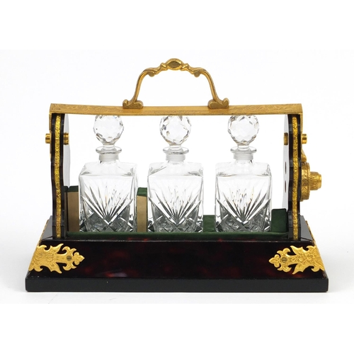 49 - Boulle work style three bottle tantalus with a gilt metal mount, 26.5cm wide...