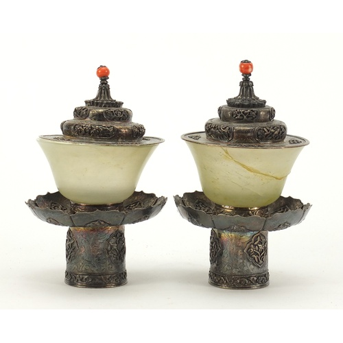 8 - Pair of Chinese green jade tea bowls with silver coloured metal stands and lids, each finely embosse...