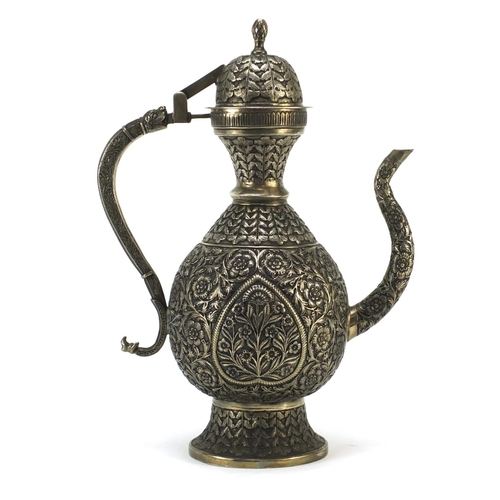4133 - Indian silver coloured metal wine ewer embossed and engraved with flowers, 36cm high...