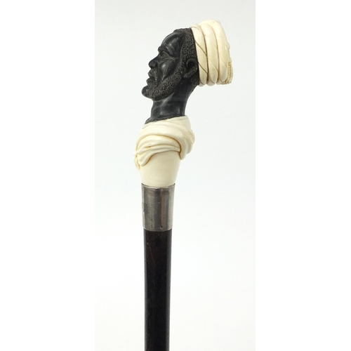 35 - Good ebonised walking stick with carved ivory and horn pommel in the form of a blackamoor, having a ...