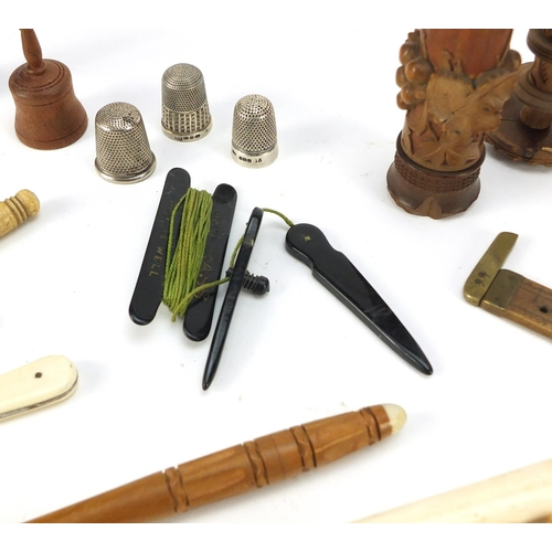 40 - Antique and later objects including ivory whistle, silver thimble, treen needle cases, brass tape me...