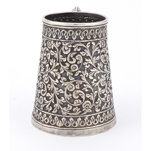 165 - Indian unmarked silver tankard of conical form, profusely embossed with flowers and foliage, 9cm hig...