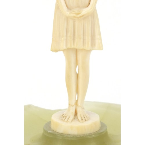 129 - Art Deco carved ivory figure of a young girl mounted on an onyx dish, 13cm high...