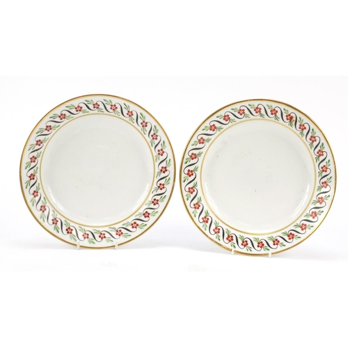 Pair of 19th century French porcelain plates with floral borders, 24.5cm in diameter