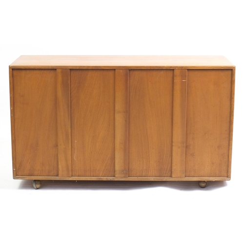 1307 - Ercol Windsor elm sideboard with three cupboard doors above two drawers, 76cm H x 130cm W x 43cm D...