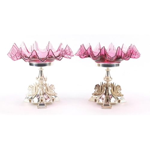 48 - Pair of silver plated and ruby glass tazzas cast with mythical winged creatures, numbered 2832, 25cm...