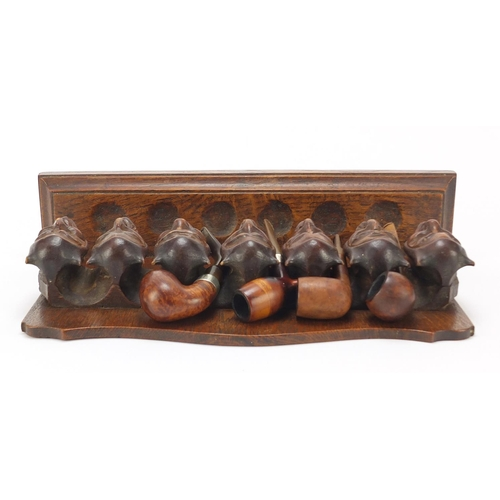 54 - Carved oak devil head design pipe stand with four pipes including two with silver mounts, the rack 3...