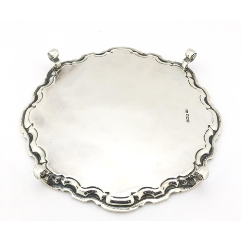 21 - Atkin Brothers, Georgian style silver salver raised on four scroll feet, Sheffield 1935, 20.5cm in d...