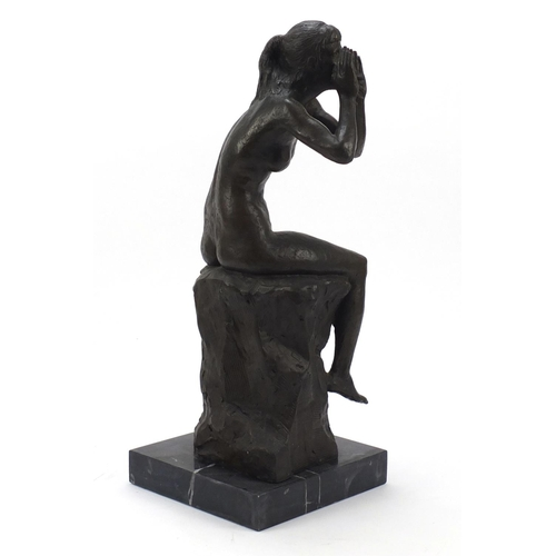 108 - Large patinated bronze figure of a seated nude female raised on a square black marble base, 53cm hig...