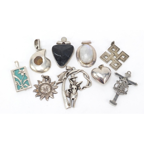 Nine silver pendants including a fossilised ammonite, love heart and crucifix, the largest 6.5cm in length, 115.2g