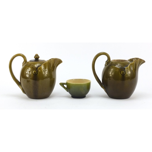 59 - Linthorpe, two Arts & Crafts pottery jugs and a cup with saucer having green glazes in the manner of...