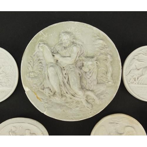 24 - Seven Italian Grand Tour plaster cameos, the largest 7.5cm in diameter...