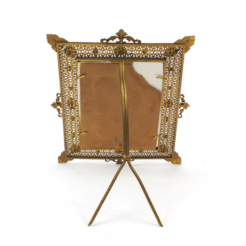 23 - Ornate pierced brass easel photo frame set with turquoise and red cabochons, 21.5cm high x 16cm wide...