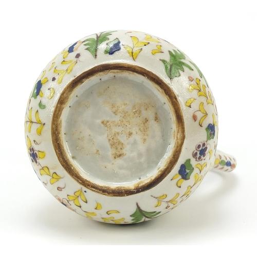 53 - Turkish Kutahya pottery coffee pot hand painted with flowers amongst foliage, 21cm high...