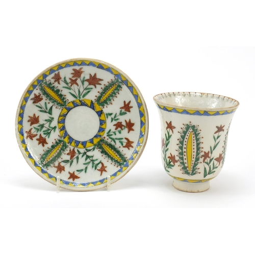 54 - Turkish Kutahya pottery cup and saucer hand painted with flowers, the cup 10cm high...