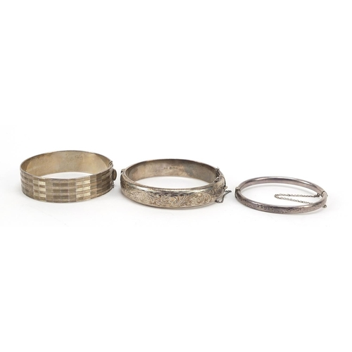 Three silver hinged bangles including two Victorian style engraved with flowers, total 55.0g