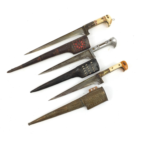 Three Indo-Persian Khyber knives, including two with ivory grips and sheaths, one embossed with flowers, the largest 39cm in length