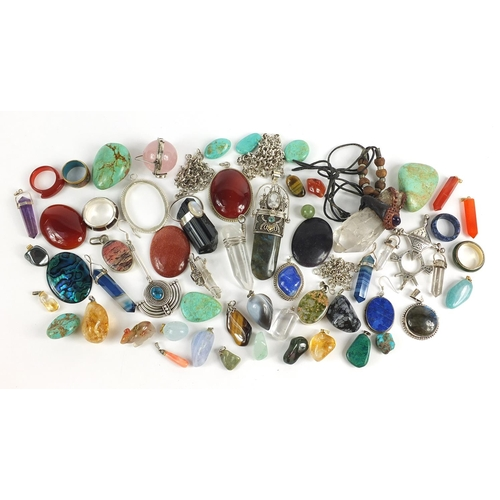 Selection of spiritual healing crystal pendants and stones, some with silver mounts