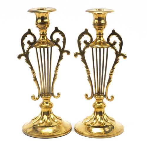 21 - Pair of classical brass lyre design candlesticks, each 29.5cm high...