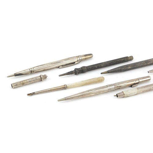 24 - Nine silver propelling pencils and pens, the largest 13cm in length...