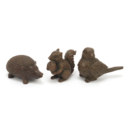 Three Japanese patinated bronze animals comprising hedgehog, bird and squirrel, each with impressed marks to the base, the largest 5cm in length