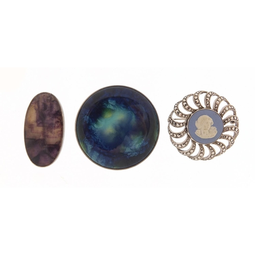 Three silver brooches comprising Blue John, Wedgwood marcasite and Ruskin design, the largest 4.7cm in diameter