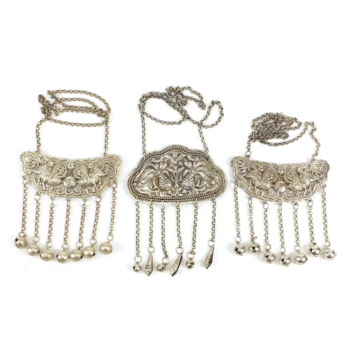 Two Chinese silver coloured metal embossed pendants with bells, each approximately 11cm wide