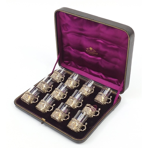 Set of twelve Victorian silver glass holders embossed with cherubs at play and fitted with eleven glass inserts (one glass insert missing), housed in a velvet lined fitted case, Birmingham 1892, each glass 5cm high