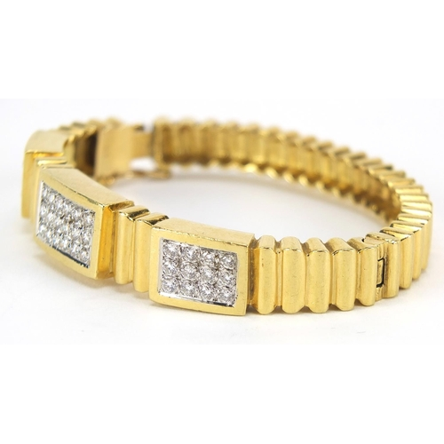 33 - 18ct gold diamond cluster hinged bangle, set with forty two diamonds the diamonds approximately 2.2m...