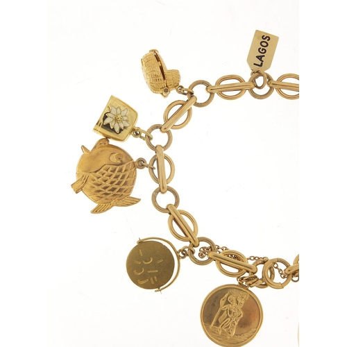 40 - 9ct gold charm bracelet with a selection of mostly gold charms including St Christopher, Dutch clog ...